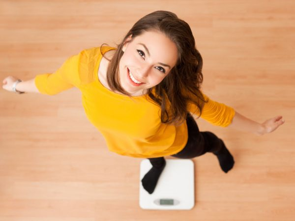 Portrait of young brunette beauty using household scale.
