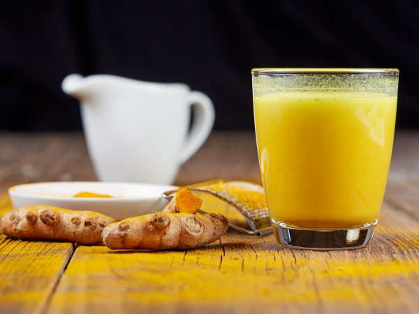 Turmeric tea golden milk with orange curcuma root on wooden table